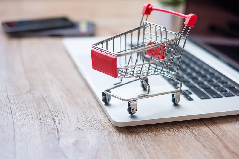 Shopping cart on laptop at home office. business, e-business, technology, e-commerce, digital banking and online payment concept